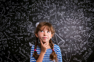 Thinking girl in blue striped t-shirt with two braids with finger on her cheek against big blackboard with mathematical symbols and formulas