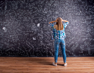 Thinking student in blue checked shirt holding her head against big blackboard with mathematical symbols and formulas, back view, rear view