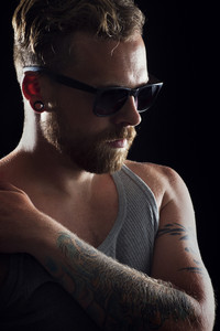 Thinking young man / rocker with ear rings, tattoo and sunglasses.