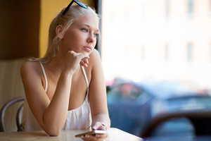 Thinking young woman looking out the window