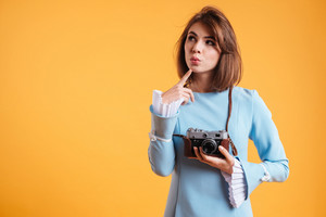 Thoughtful lovely young woman holding old vintage camera and thinking over yellow background