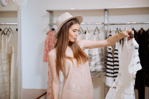 Thoughtful pretty young woman in hat holding and looking at dress in clothing store
