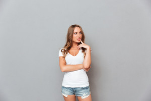 Thoughtful pretty young woman standing and thinking over gray background