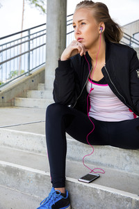 Thoughtful Sporty Woman Listening Music While Sitting On Steps