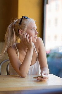 Thoughtful teenage girl looking out the window