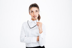 Thoughtful young business woman holding glasses and thinking over white background