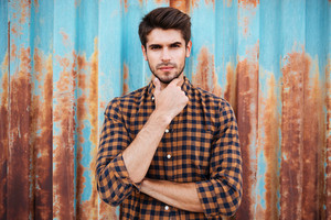 Thoughtful young man in plaid shirt thinking and touching his chin over blue metal background with rust