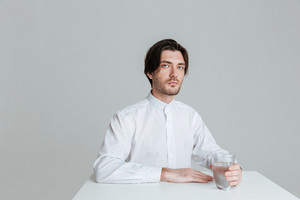 Thoughtful young man sitting at the table holding water glass isolated on the gray background