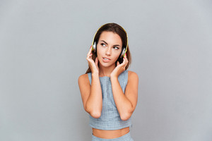 Thoughtful young woman in headphones listening to music over grey background