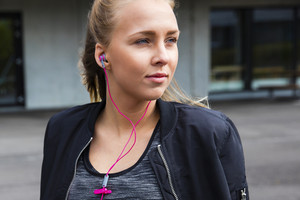 Thoughtful Young Woman In Sportswear Listening To Music