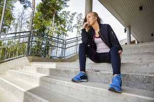 Thoughtful Young Woman In Sportswear Sitting On Steps