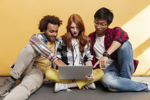 Three amazed young people using and pointing on the screen of laptop together over yellow background