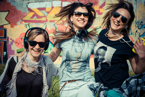 three beautiful friends authentic in urban contest listening to music