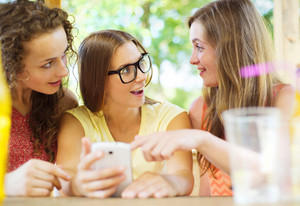 Three beautiful girls drinking and having fun with smartphone in pub garden