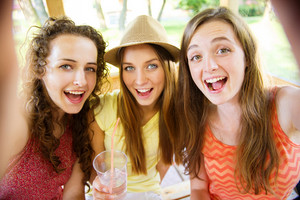 Three beautiful girls drinking and taking selfie with smartphone in pub garden