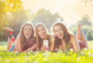 Three beautiful girls laughing together and lying on grass outdoors in a park.