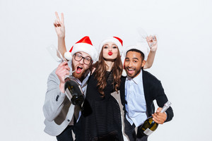 Three cheerful young people with bottles of champagne and glasses celebrating new year over white background