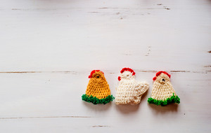 Three colorful crocheted Easter chickens against old white wooden background