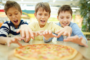 Three funny boys eating pizza in cafe