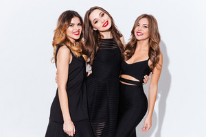 Three happy attractive young women in black dresses standing together over white background