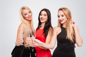 Three happy charming young women celebrating and drinking champagne together over white background