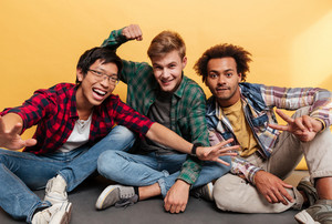 Three happy excited young men friends having fun together over yellow background