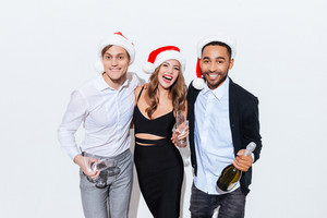 Three happy friends in santa claus hats with bottle of champagne over white background