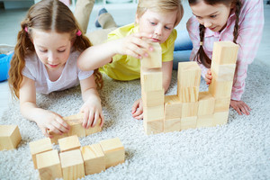 Three little friends playing with wooden bricks