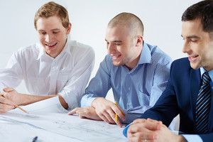 Three male architects discussing sketch at meeting