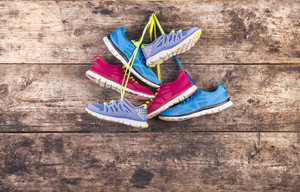 Three pairs of running shoes hang on a nail on a wooden fence background