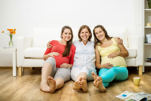 Three pregnant women sitting in front of sofa