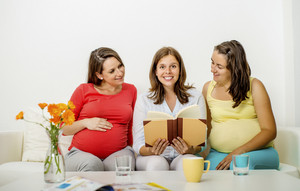 Three pregnant women sitting on sofa and posing