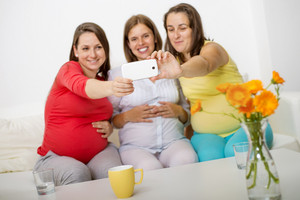 Three pregnant women sitting on sofa, smiling and taking selfie