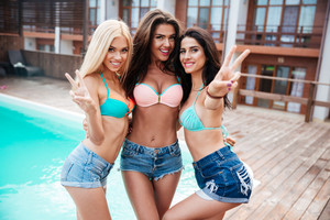Three smiling pretty girls standing near swimming pool and showing peace sign