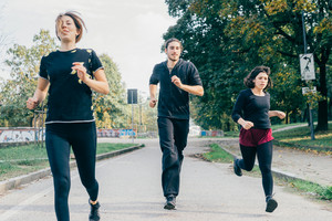 Three women and man runners running outdoor in city park in autmun - runners, training, athlete concept