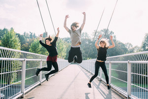 Three young beautiful caucasian women and man jumping outdoor in city back light - achievement, goal, satisfaction concept