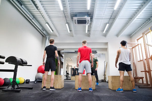 Three young fit men in crossfit gym with their personal trainer doing box squats, practicing box jumps. Rear view.