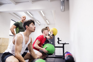 Three young fit men in crossfit gym with their personal trainer exercising with medicine balls.