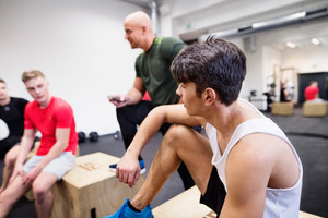 Three young fit men in crossfit gym with their personal trainer resting after doing box jumps.