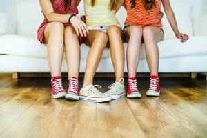 Three young girls sitting on sofa, closup on legs and sneakers