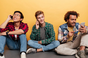 Three young men friends talking on mobile phone over yellow background
