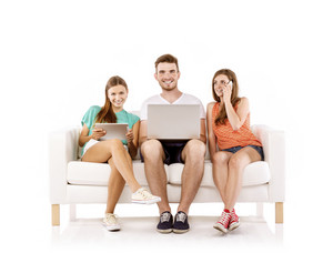 Three young people sitting on sofa and using wireless technologies, isolated on white background. Best friends
