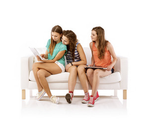 Three young women sitting on sofa and using digital tablet, isolated on white background. Best friends