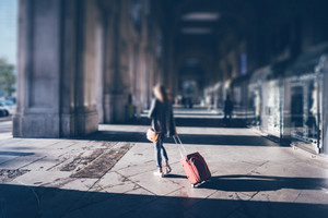 Tilt shift photo of a young girl with red luggage exit from Milan Central Station - travel, holiday, trip concept