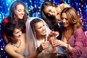 Tilt up shot of friends drinking champagne to the bride's health, bridal party