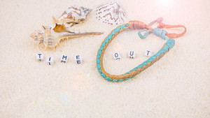 Time out letters in front of sea shells and coloured wristbandon on sandy beach