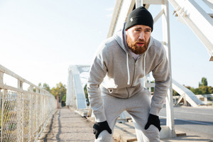 Tired bearded sports man resting after workout outdoors at the city bridge