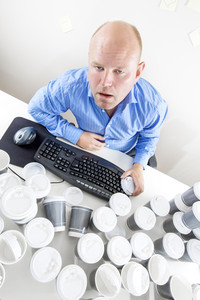 Tired businessman drinks too much coffee at office