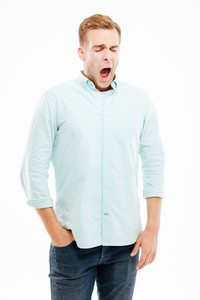 Tired exhausted young man standing and yawning over white background
