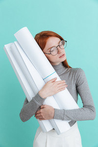 Tired redhead young woman with closed eyes holding and huging blueprints over blue background